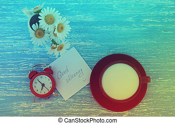 Daisy flowers, alarm clock and cup of milk with good morning note on rustic blue wooden background. Photo in vintage style