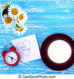 Daisy flowers, alarm clock and cup of milk with good morning note on rustic blue wooden background