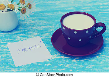 Daisy flowers and cup of milk with I love you note on rustic blue wooden background. Photo in vintage style