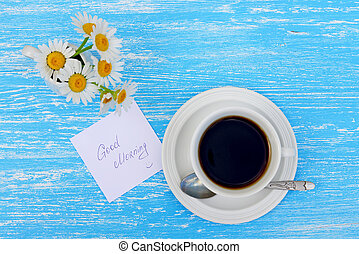 Daisy flowers and cup of tea with good morning note on rustic blue wooden background