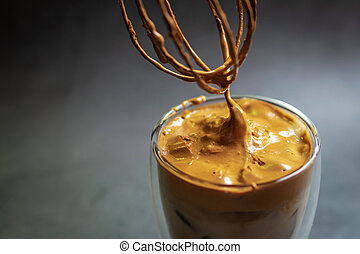 Dalgona Coffee; fluffy whipped coffee on milk. Coffee is a beverage made by whipping equal proportions of instant coffee, sugar and hot water until it becomes creamy and adding it to cold or hot.