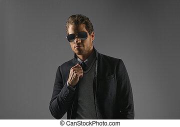 dall'aspetto, confident., fiducioso, giovani uomini, in, occhiali da sole, standing, isolato, su, grigio