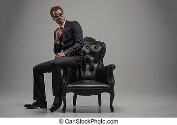 dall'aspetto, giusto, perfect., piena lunghezza, di, fiducioso, giovane, uomini affari, in, occhiali da sole, seduta, su, il, vendemmia, sedia, mentre, isolato, su, grigio