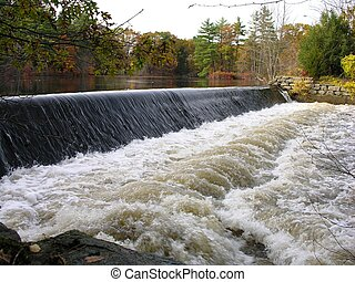 Dam with rushing water in fall.