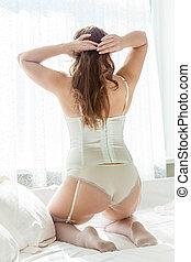 dama, en, lenceria, arrodillar, en cama, contra, ventana