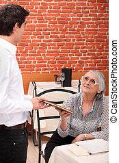 dama madura, ser, servido, por, camarero, en, restaurante