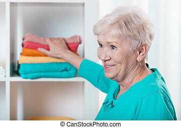 dama, poniendo, toallas