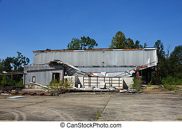 Business in Ruston, Louisiana, is damaged from tornado or wind storm.  Tin roof is collapsed and siding blown away.
