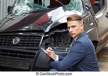 Well dressed insurance assessor inspecting damaged vehicle
