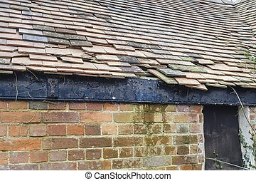 Damaged clay roof tiles on a pitched roof, UK