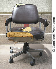 Damaged office chair with teared black leather