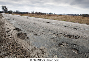 Damaged road - Badly damaged country asphalt road after...