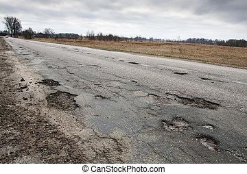 Damaged road - Badly damaged country asphalt road after...