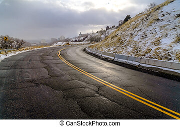 Damaged road on snowy hill in Salt Lake City