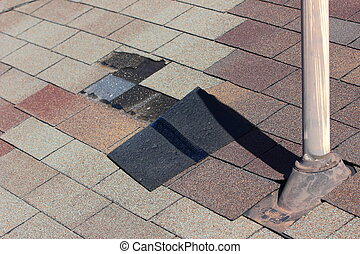 Damaged Roof - A close up view of shingles being blown off a...