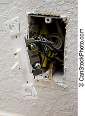 A close up on a light switch with damaged wiring