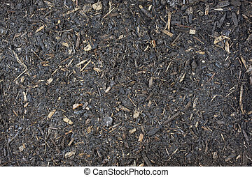 damp garden potting soil background with small wood chips...