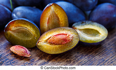 Damson plums - Halved plum and other whole plums on the ...
