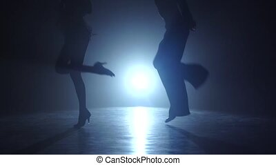 Dance couple demonstrating magnificent choreography of rumba, visible only legs, studio illuminated with white spotlight, dressed in costumes, man and girl isolated on black background, slow motion, smoke, close ups