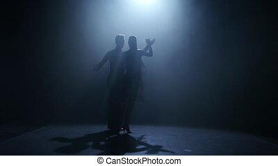 Dance element from the ballroom-sport program, silhouette couple ballroom, smoke