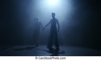 Dance element from the jive, silhouette couple ballroom. Smoke background