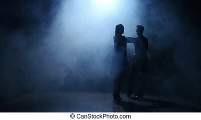 Dance element from the latina, silhouette couple ballroom. Smoke background