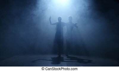 Dance element from the salsa, silhouette couple ballroom. Smoke background