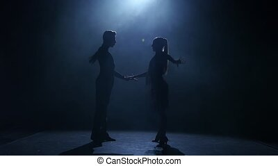 Dance element from the samba, silhouette couple ballroom. Black background