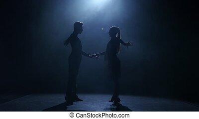 Dance element from the samba, silhouette couple ballroom. Black background