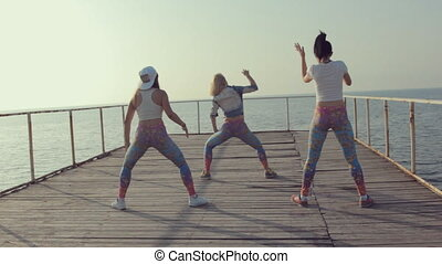 Dance Hall by adolescent girls on a wooden quay near the sea...