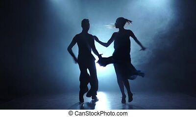Dance the latina performed by a professional couple in slow motion, dancers graceful posing in smoky studio illuminated with spotlight, man and girl dressed in dance costumes, black background, silhouette