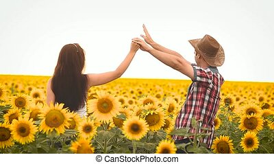 dance man in a hat and a girl on the field with yellow sunflowers