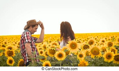 dance man in and a girl a hat, on field with yellow sunflowers
