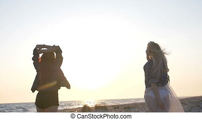 dance on the beach of two young sexy women dressed in boho style in the sunset light over the sea