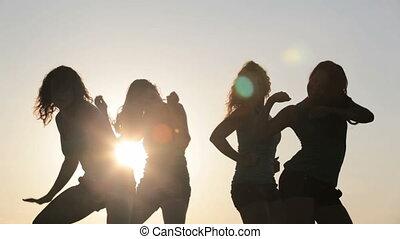 Dance over sun - Three slim women dancing over sun on the...