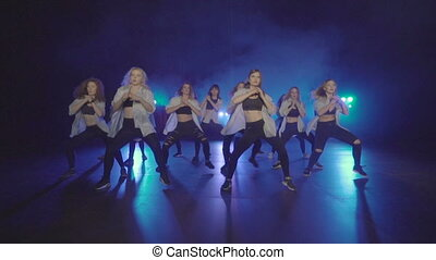 Dance performance of pretty female group on a dark stage with blue lights and smoke