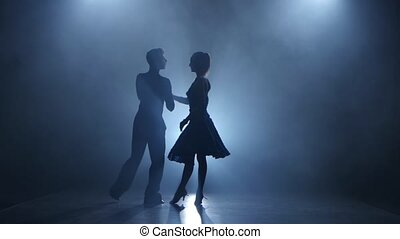 Dance rumba performed by professional couple in smoky studio, silhouette