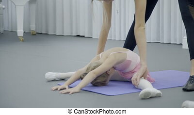 Dance studio teacher helps little girl make bend in back....