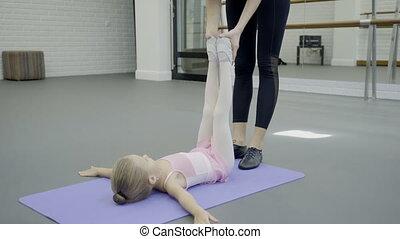 Dance teacher puts legs of lying little girl in right position.