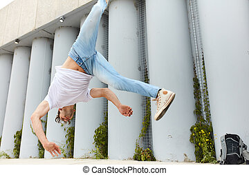 dancer doing a movement, man falling down while performing a flip