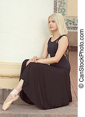Dancer in a black dress and sitting