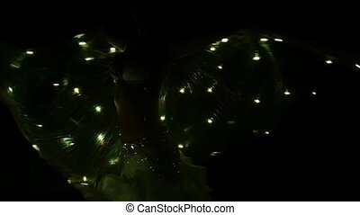 Dancer in a costume with bright lanterns spinning. Black background. Sihouette. Slow motion
