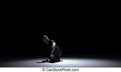 Dancer in dark suit continue dancing breakdance, on black, shadow, slow motion