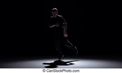 Dancer in dark suit dancing breakdance, on black, shadow, slow motion