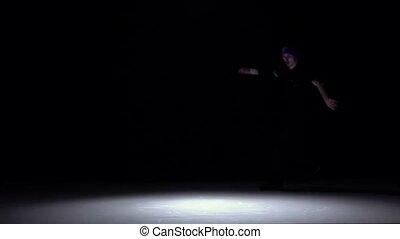 Dancer in dark suit go on dancing breakdance, on black, shadow, slow motion
