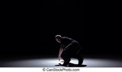 Dancer in dark suit starts dancing breakdance, on black, shadow, slow motion