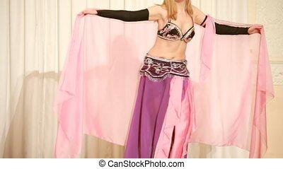 Dancer in rose dress make rhythmic moves, closeup view