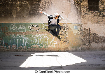 Dancer jumping in urban setting - Young male hip hop dancer...