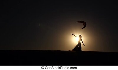 Dancer makes sexual movements with her body. Silhouette....