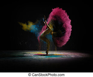 Dancer moving in cloud of coloured dust on scene -...